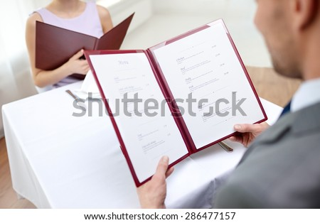 restaurant, food, eating and holiday concept - close up of couple with menu choosing dishes at restaurant #286477157