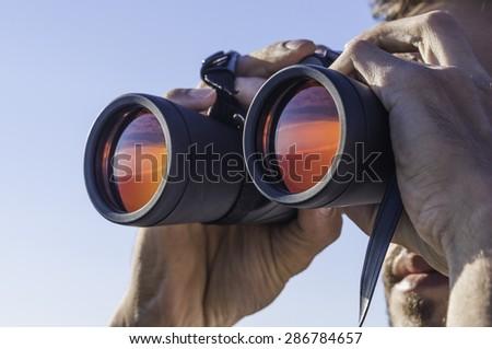 A man looking through the binoculars  Royalty-Free Stock Photo #286784657