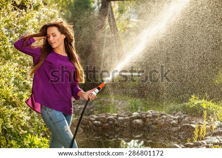Beautiful joyful young girl in violet casual shirt poses in a summer garden with water hose. #286801172