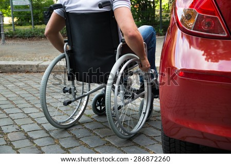 Close-up Of A Man Sitting On A Wheelchair Near His Car Royalty-Free Stock Photo #286872260