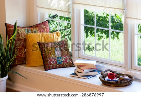 Cup of Coffee on a Tray, Piled Books and Square Pillows at the Reading Corner Inside the House. #286876997
