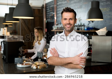 Successful small business owner standing with crossed arms with employee in background preparing coffee Royalty-Free Stock Photo #286965218