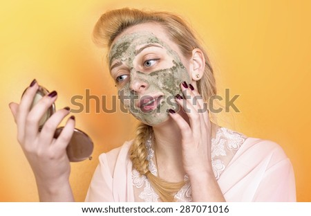 Girl puts a mask on his face in the mirror #287071016