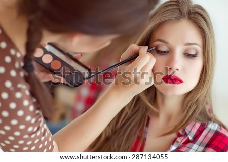 make up artist doing professional make up of young woman Royalty-Free Stock Photo #287134055