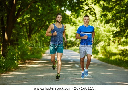 Two friends running through the forest on a jogging trail #287160113