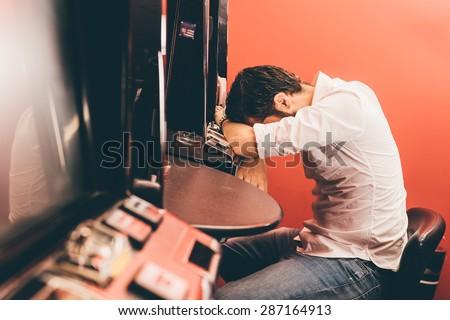 Man losing at slot machines in casino Royalty-Free Stock Photo #287164913