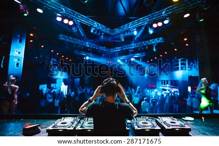 DJ with headphones at night club party under the blue light and people crowd in background Royalty-Free Stock Photo #287171675