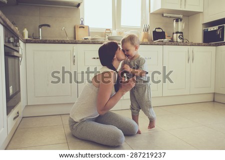 Mom with her 2 years old child cooking holiday pie in the kitchen to Mothers day, casual lifestyle photo series in real life interior #287219237