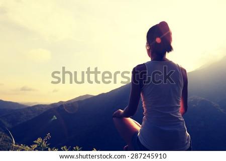 young yoga woman at sunrise mountain peak #287245910
