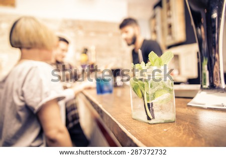 close up on a cocktail in a bar. barman and customers are standing in the back. concept about bar, profession and people. #287372732