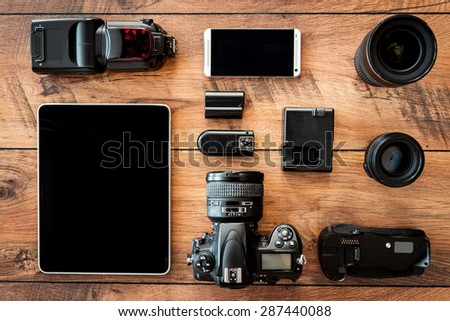 Photo equipment. Top view of diverse personal equipment for photographer laying on the wooden grain #287440088