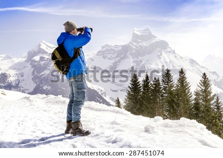Man with backpack is standing on a mountain and looking through binoculars. #287451074