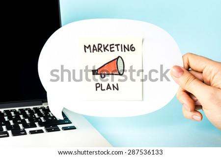 Marketing Plan on post-it note and white speech bubble, with notebook and blue background, and megaphone.