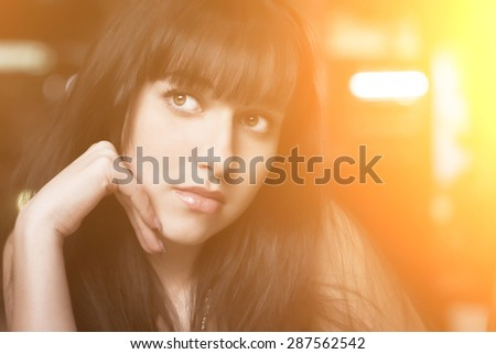 Young beautiful brunette woman. Close-up portrait with sunshine effect. #287562542