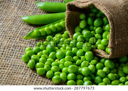 hearthy fresh green peas and pods on rustic fabric background #287797673
