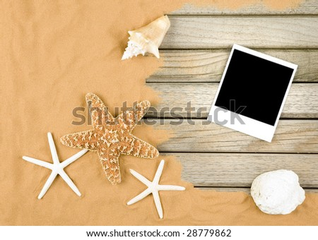 sand and wood background with instant photo frame