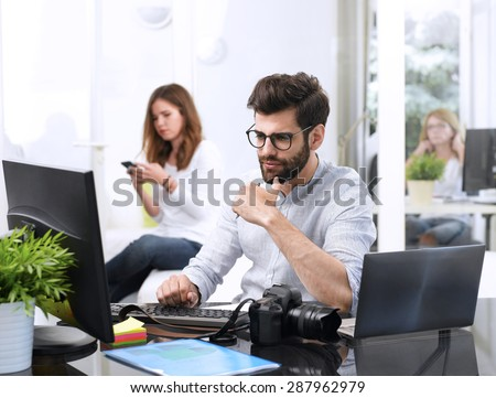 Portrait of young designer sitting at graphic studio in front of laptop and computer while working online. Assistant using her mobile at background.