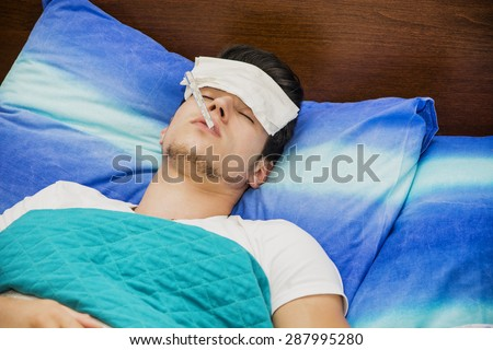 Young handsome man in bed with a flu or measuring fever with thermometer in his mouth #287995280
