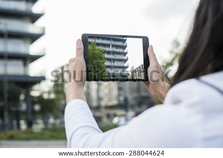 Woman taking picture with her ipad mini.A young woman is holding a digital tablet. The image is taken in the city. The young woman has long brown hair. The face of the young woman is not visible.