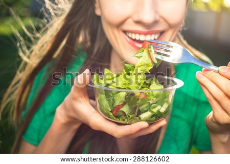 Portrait of attractive caucasian smiling woman eating salad, focus on hand and fork. soft, backlight Royalty-Free Stock Photo #288126602
