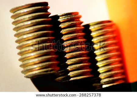 Closeup image of three colorful steel bolts in parallel showing sharp grooves, on white background. Industrial photography. Product photography.