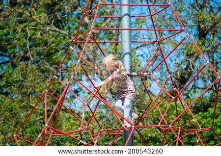 girl climbing up on a playground #288543260