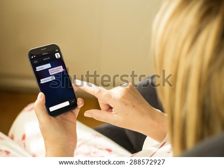 wireless communications and social concept: woman with a 3d generated smartphone with instant messaging on the screen. All screen graphics made up. Royalty-Free Stock Photo #288572927