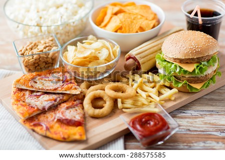 fast food and unhealthy eating concept - close up of fast food snacks and cola drink on wooden table Royalty-Free Stock Photo #288575585