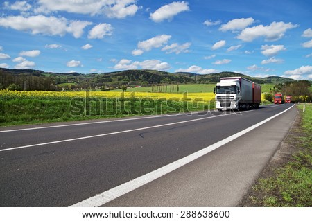 Trucks driving on the asphalt road around the yellow flowering rapeseed field in rural landscape. Wooded mountains in the background. Blue sky with white clouds. #288638600