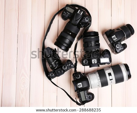 Modern cameras on wooden table, top view #288688235