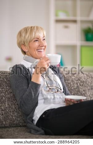 Senior woman sitting on sofa smiling and drinking tea #288964205