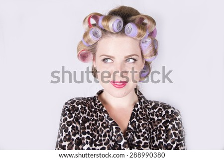 Beautiful blonde woman with curlers wearing a leopard print bathrobe (studio, white background)