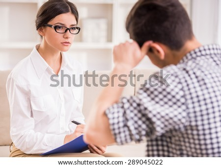Man having a conversation with his psychotherapist on couch in office. #289045022