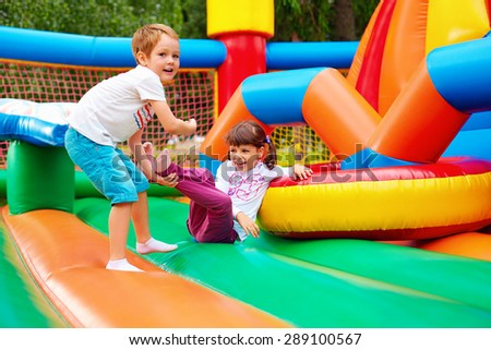 happy kids having fun on inflatable attraction playground #289100567
