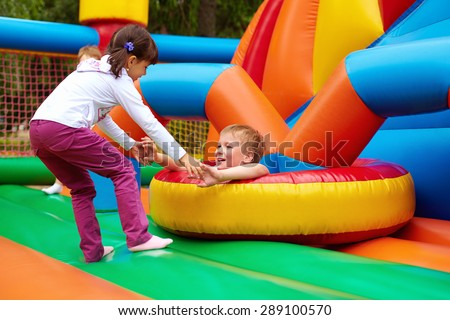 happy kids having fun on inflatable attraction playground #289100570