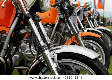 Row of motorbikes in a field #289249946