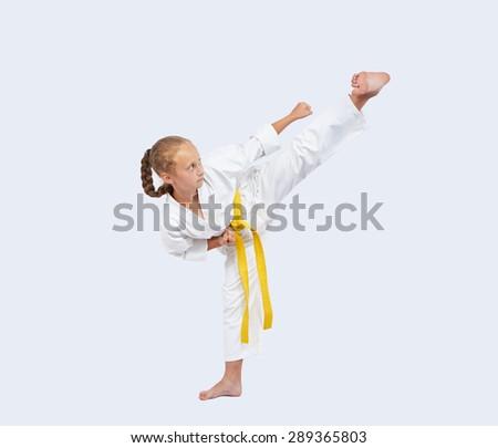 On a light background sportswoman beats blow leg #289365803