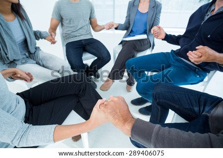Group therapy in session sitting in a circle in a bright room #289406075