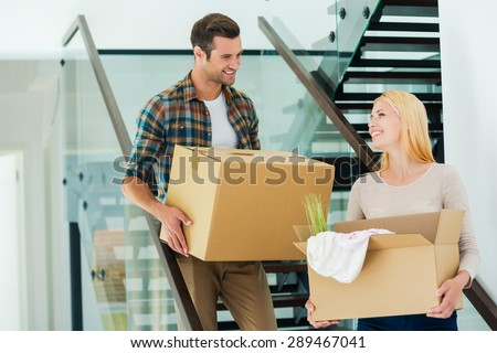 Happy to do everything together. Happy young couple holding cardboard boxes while going down the stairs  #289467041