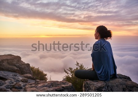 Rear view of a young woman sitting on a mountain top peacefully gazing at low-lying morning clouds and the pastel colours of a tranquil sunrise Royalty-Free Stock Photo #289501205