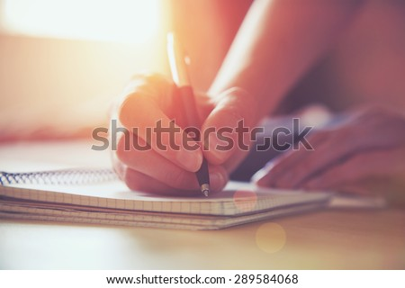 female hands with pen writing on notebook #289584068