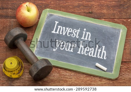 Invest in your health -  slate blackboard sign against weathered red painted barn wood with a dumbbell, apple and tape measure Royalty-Free Stock Photo #289592738