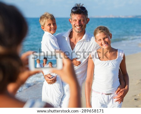 Mother taking family picture with father and two children at the tropical beach. Focus on the family