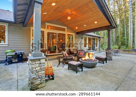 Large back yard with grass and covered patio with fire pit. #289661144