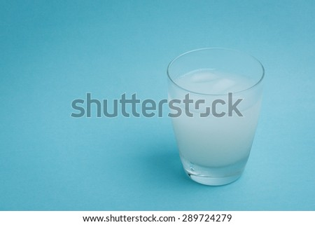 A white iced drink in a glass on a light blue background. #289724279