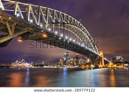 East side of Sydney harbour bridge at sunset with bright illumination of steel arch and columns reflecting in the blurred waters of harbour with Sydney city CBD in the background Royalty-Free Stock Photo #289779122
