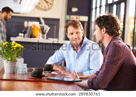 Two men meeting at a coffee shop Royalty-Free Stock Photo #289830761
