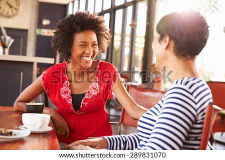 Two female friends talking at a coffee shop Royalty-Free Stock Photo #289831070