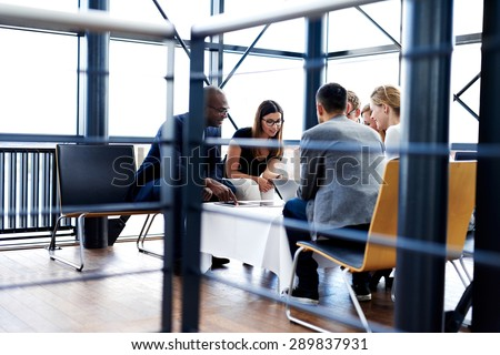 Group of executives sitting and working together using tablets and laptop Royalty-Free Stock Photo #289837931