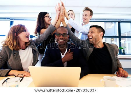Group of executives smiling and group high fiving over black colleague's head #289838837